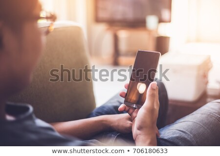 mobile phone display in focus man holding device with fingers stock photo © adamr