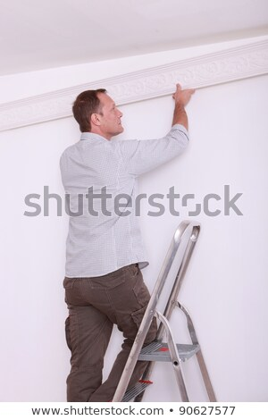 Decorator fitting coving to a ceiling Stock photo © photography33