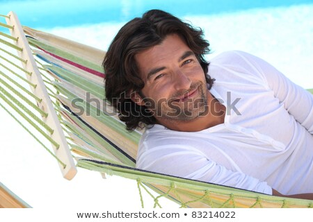 Man resting in hammock next to swimming pool Stock photo © photography33