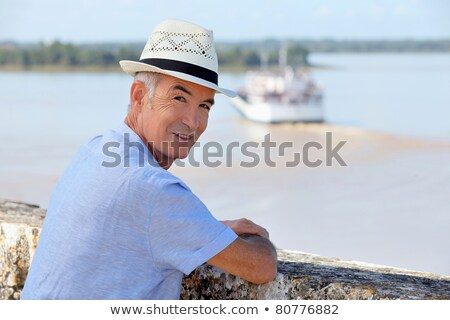 Stockfoto: Man In A Straw Hat Watching A Ferry Cross The Gironde Estuary
