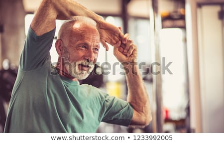 Grey-haired man stretching in the gym Stock photo © photography33