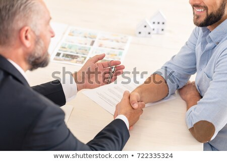 Smiling businessman handing keys  Stock photo © Rugdal