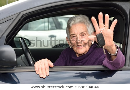 Stock photo: Smiling senior woman in a car