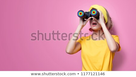 cute woman holding binoculars yellow background stock photo © pxhidalgo