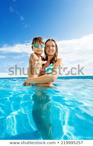 mother with child is enjoing the fresh water in the pool and bot Stock photo © meinzahn
