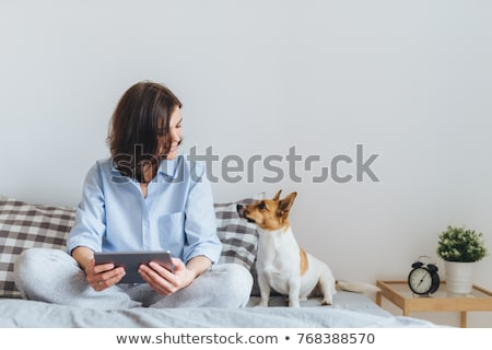 young woman sitting on the bed and holding alarm clock stock photo © deandrobot