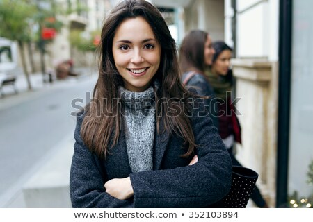 Stock photo: Young beautiful woman looking at camera in the street.