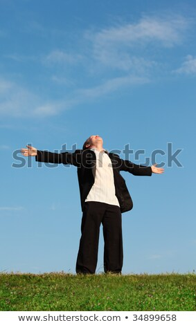 young man stands on meadow thrown back head with stretching hand Stock photo © Paha_L