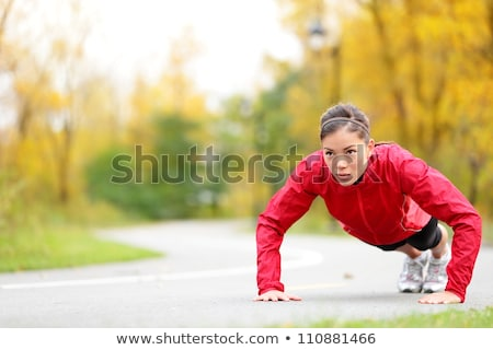 young woman doing pushups outdoors stock photo © sumners