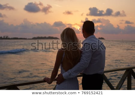 Back view of a married couple hugging on the beach Stock photo © deandrobot