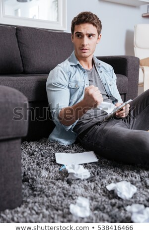 man holding crumpled sheet of paper with notepad at home stock photo © deandrobot