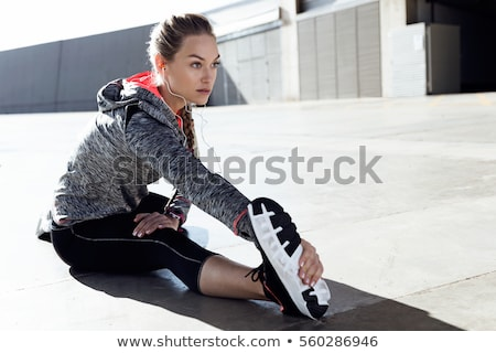 full length portrait of a fitness young woman doing stretching stock photo © deandrobot