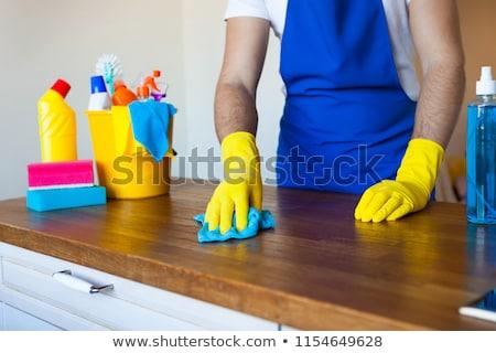 Closeup Of Young Man Wearing Apron Cleaning Kitchen Worktop Stock photo © Yatsenko