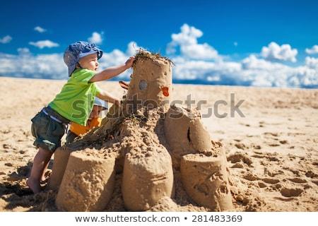 Friends building sandcastle on beach. Stock photo © RAStudio