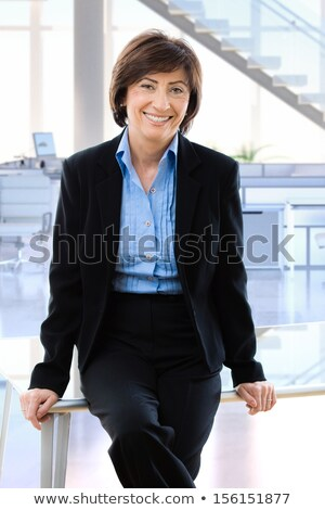 Portrait of a happy smiling mature woman leaning on desk Stock photo © deandrobot