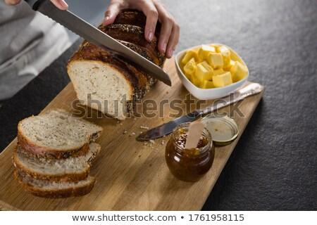 Woman cutting freshly baked multigrain bread Stock photo © wavebreak_media