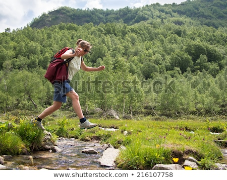 girl jumping over creek Stock photo © IS2