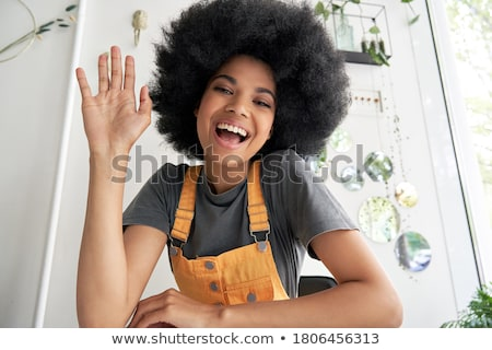 Young woman waving to camera Stock photo © IS2