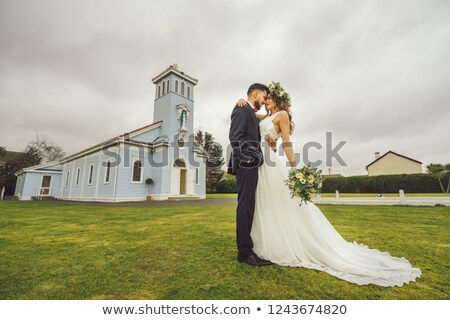 groom kisses bride outside church stock photo © is2