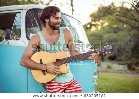 Man leaning on campervan and playing guitar Stock photo © wavebreak_media