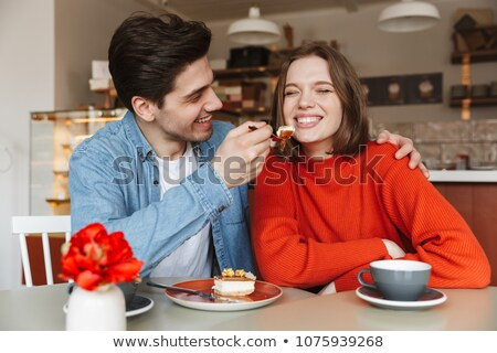 Foto stock: Family Portrait Of Happy Couple Eating Sweets While Man Feeding