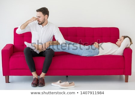 Loving couple lying down on the sofa in the room Stock photo © boggy