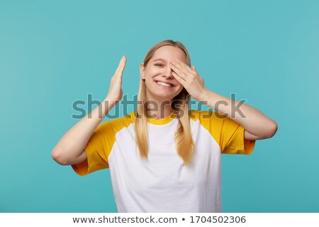 Photo of positive blond woman in basic clothing covering eyes wi Stock photo © deandrobot