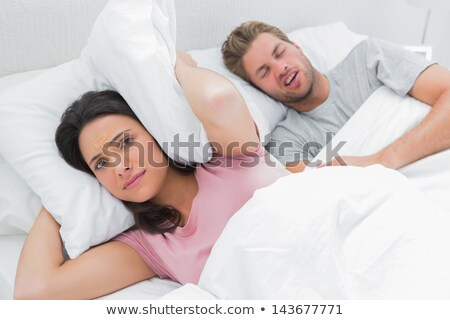 woman blocking ears while man snoring on bed Stock photo © Lopolo