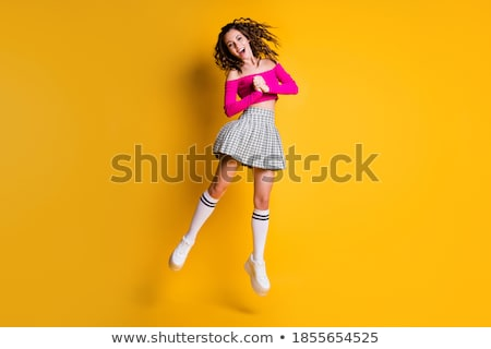 Crop of stylish young girl with long brunette holding white hand bag. Posing at camera. Wearing blue stock photo © studiolucky