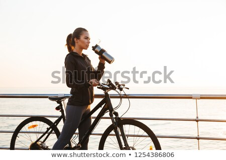 Photo of attractive woman riding bicycle on boardwalk, during su Stock photo © deandrobot