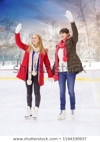 happy female friends waving hands on skating rink Stock photo © dolgachov