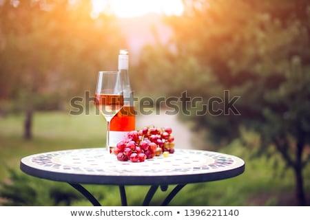 one bottle of rose wine in autumn vineyard on marble table stock photo © dashapetrenko