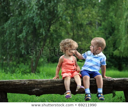 happy family sitting on bench in park stock photo © lopolo