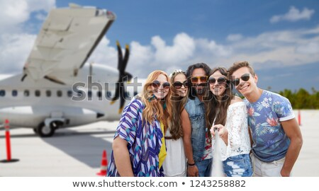 friends taking picture by selfie stick on airfield Stock photo © dolgachov