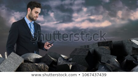 dark bricks in pile with businessman holding phone stock photo © wavebreak_media