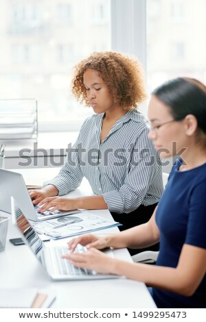 Young serious mixed-race banker touching keys of laptop keypad at workplace Stock photo © pressmaster