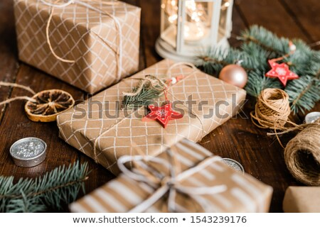 Wrapped giftboxes surrounded by conifer, candles, decorations and threads Stock photo © pressmaster