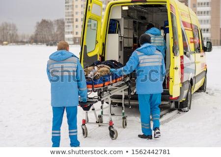 Paramedics pushing stretcher with fixed unconscious man into ambulance car Stock photo © pressmaster