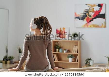 Back view of restful girl with dreadlocks sitting on sofa and listening to music Stock photo © pressmaster