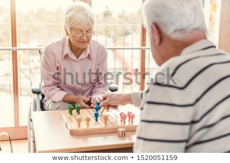 Two seniors in a nursing home playing a board game Stock photo © Kzenon