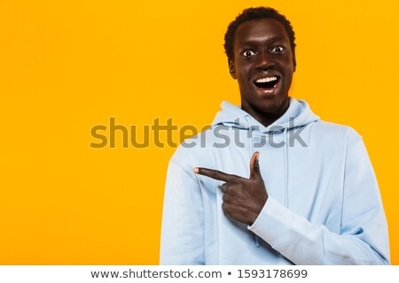 Image of optimistic african american guy smiling and pointing fi Stock photo © deandrobot