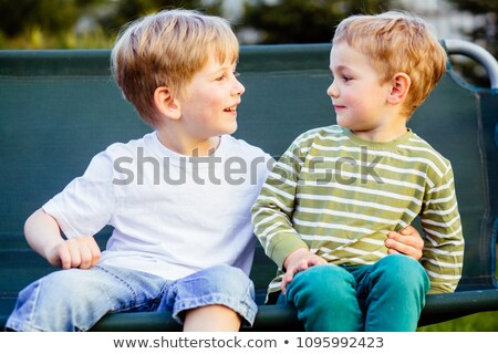 Stock photo: Two brother huging each other outdoor, smiling and laughing