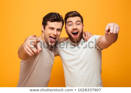 handsome guy pointing at camera stock photo © stockyimages