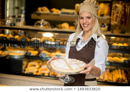 Bakery worker holding plate of fruit tarts Stock photo © photography33