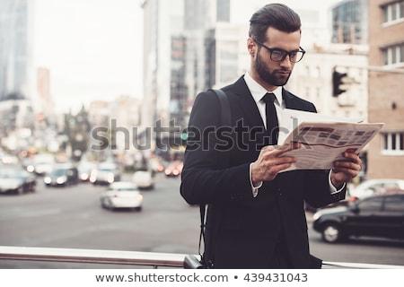Férfi újság fiatalember ül fotel otthon Stock fotó © elly_l