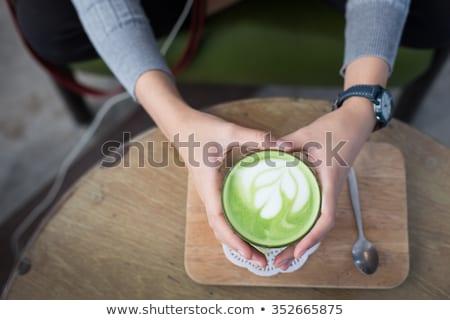 Hand on hot drink of matcha green tea latte Stock photo © nalinratphi