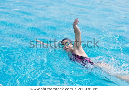 Young girl in goggles and cap swimming crawl stroke style Stock photo © lightpoet