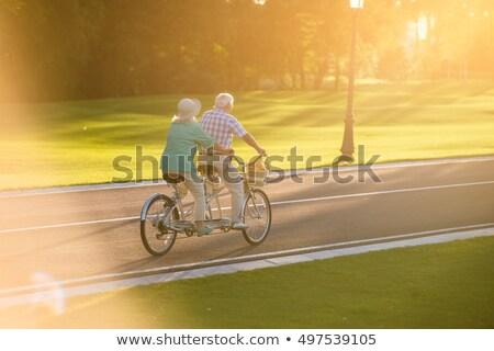 Pár lovaglás tandem bicikli kint portré Stock fotó © deandrobot