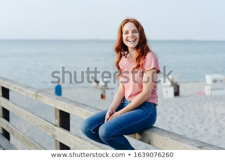 Vivacious young women sitting outdoors laughing Stock photo © dash