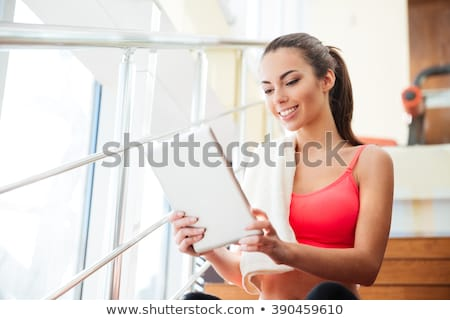 Happy cute young sportswoman using tablet in gym Stock photo © deandrobot